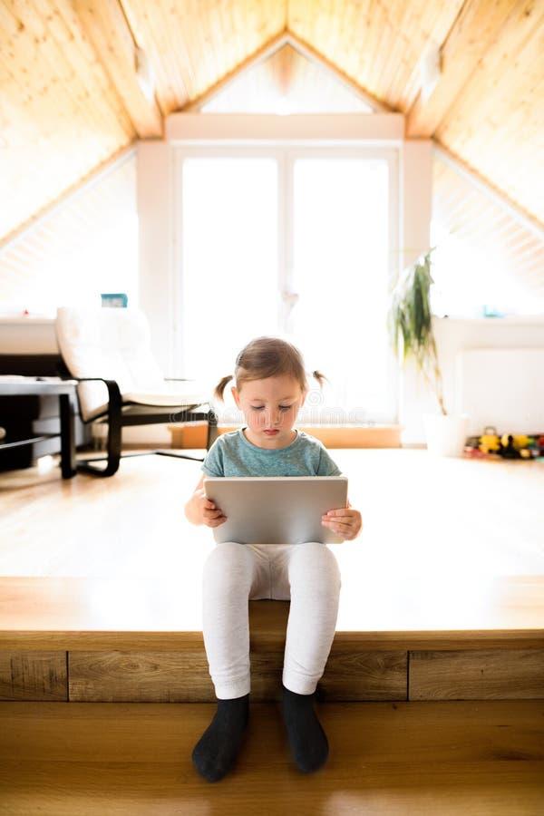Μικρό κορίτσι που προσέχει στο σπίτι κάτι στην ταμπλέτα στοκ εικόνα