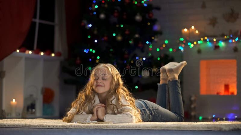 Μικρό κορίτσι που προσεύχεται στη Παραμονή Χριστουγέννων, που κάνει τις επιθυμίες, που περιμένουν τα θαύματα στοκ φωτογραφίες