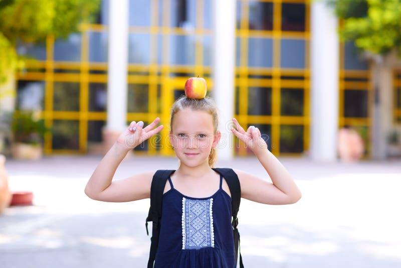 Μικρό κορίτσι που στέκεται με τη Apple στο κεφάλι της στοκ εικόνα με δικαίωμα ελεύθερης χρήσης
