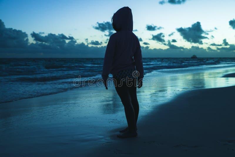 Μικρό κορίτσι που στέκεται στην ωκεάνια ακτή στο σκοτάδι στοκ φωτογραφία με δικαίωμα ελεύθερης χρήσης
