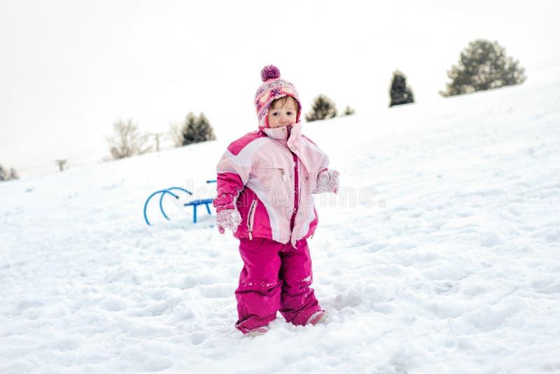 Μικρό κορίτσι που στέκεται στο χιόνι στοκ εικόνα με δικαίωμα ελεύθερης χρήσης