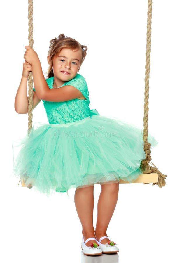 Μικρό κορίτσι που ταλαντεύεται σε μια ταλάντευση στοκ εικόνες