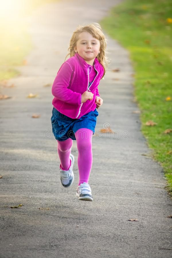 Μικρό κορίτσι που τρέχει γρήγορα στο πάρκο στοκ φωτογραφίες