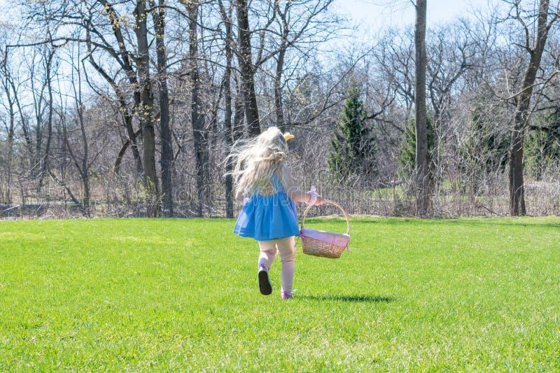 Μικρό κορίτσι που τρέχει με το καλάθι Πάσχας στοκ εικόνες