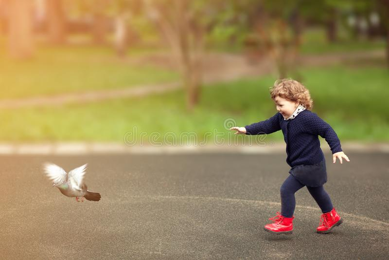 Μικρό κορίτσι που τρέχει, flaunts τα περιστέρια, παιδική ηλικία στοκ εικόνες