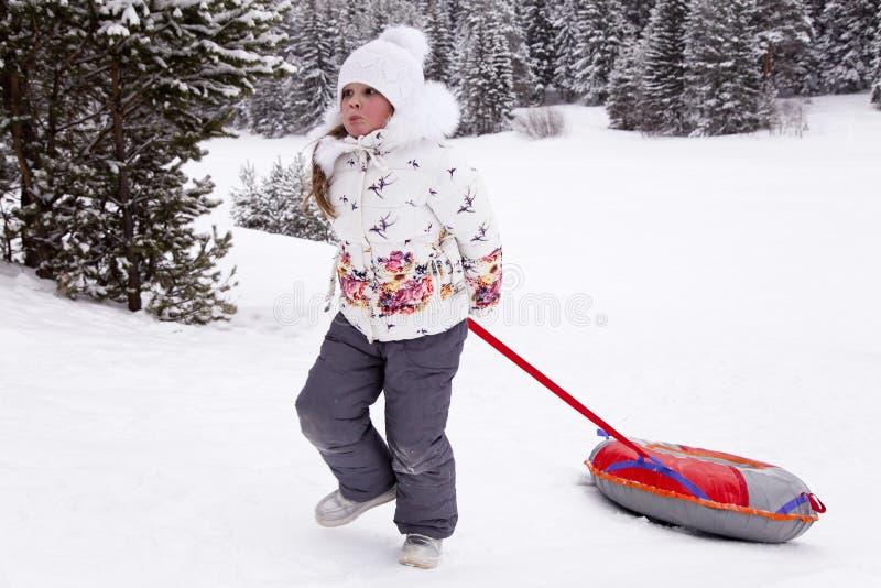 Μικρό κορίτσι που τραβά τη σωλήνωση χιονιού λουριών στοκ εικόνα