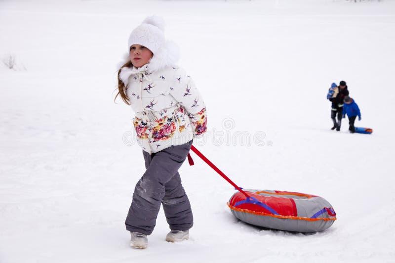 Μικρό κορίτσι που τραβά τη σωλήνωση χιονιού λουριών στοκ φωτογραφία