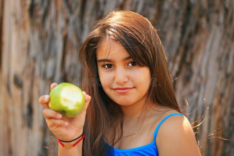 Μικρό κορίτσι που τρώει ένα πράσινο μήλο στοκ φωτογραφία