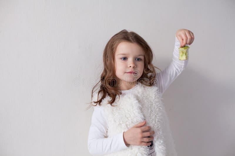 Μικρό κορίτσι που τρώει τα ώριμα πράσινα υγιή τρόφιμα της Apple στοκ εικόνες