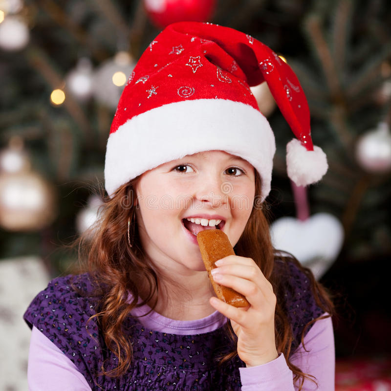 Μικρό κορίτσι που τρώει την καραμέλα Χριστουγέννων στοκ φωτογραφία με δικαίωμα ελεύθερης χρήσης