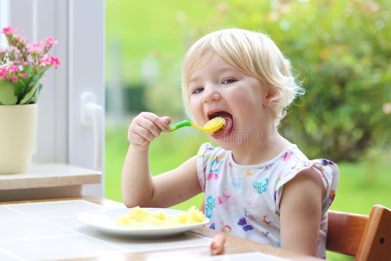 Μικρό κορίτσι που τρώει τις πολτοποιηίδες πατάτες στοκ φωτογραφία