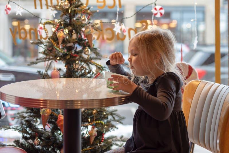 Μικρό κορίτσι που τρώει τον πάγο crem σε μια ντεμοντέ αίθουσα παγωτού στοκ εικόνες με δικαίωμα ελεύθερης χρήσης