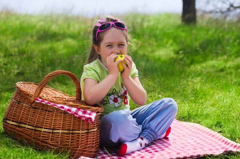 Μικρό κορίτσι που τρώει το μήλο στο πικ-νίκ στοκ εικόνες
