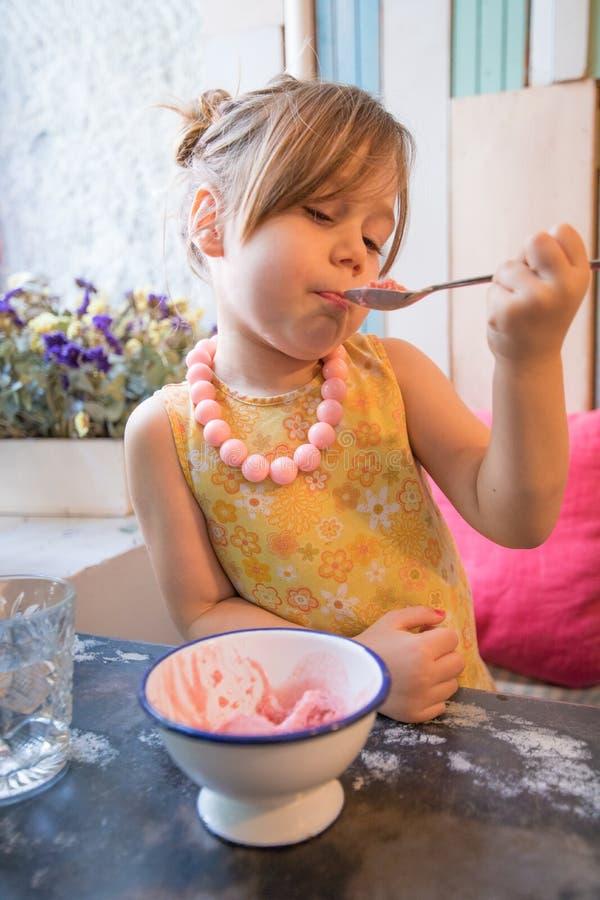 Μικρό κορίτσι που τρώει το παγωτό με το κουτάλι στο εστιατόριο στοκ φωτογραφία