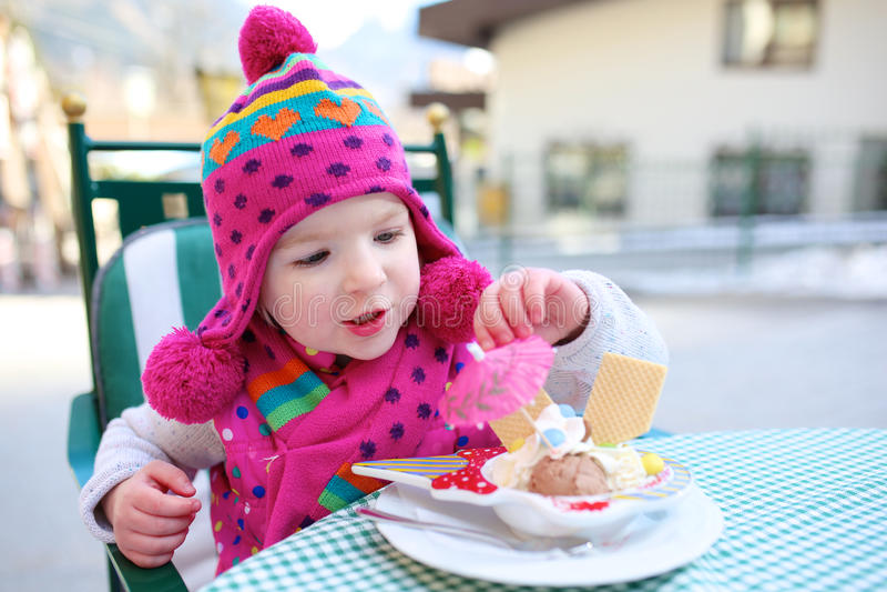 Μικρό κορίτσι που τρώει το παγωτό υπαίθρια στον καφέ στοκ φωτογραφία