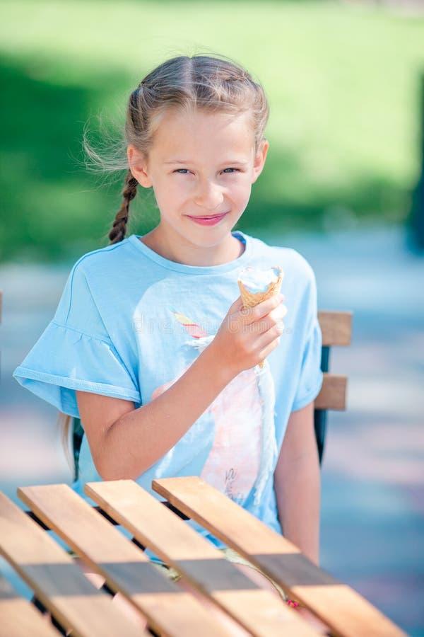 Μικρό κορίτσι που τρώει το παγωτό υπαίθρια στο καλοκαίρι στον υπαίθριο καφέ στοκ φωτογραφία