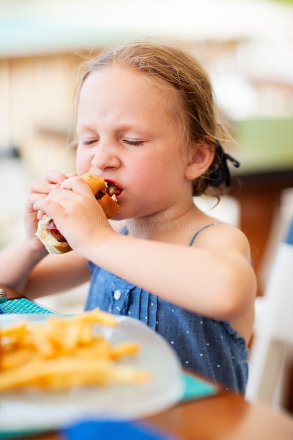 Μικρό κορίτσι που τρώει το χοτ-ντογκ στοκ φωτογραφία με δικαίωμα ελεύθερης χρήσης