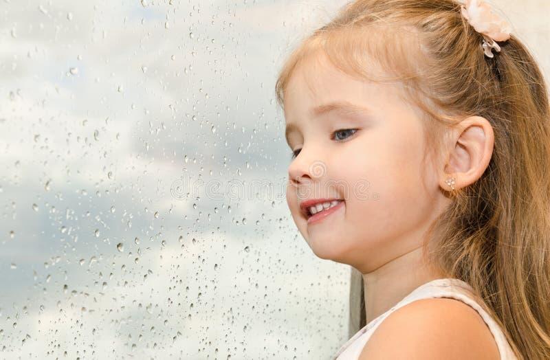 Μικρό κορίτσι που φαίνεται έξω το παράθυρο μια βροχερή ημέρα στοκ φωτογραφίες με δικαίωμα ελεύθερης χρήσης