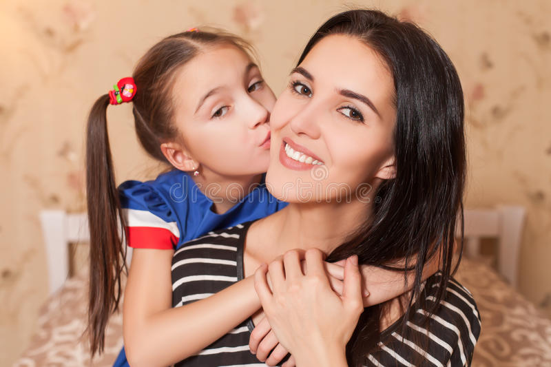 Μικρό κορίτσι που φιλά τη μητέρα της στοκ εικόνες