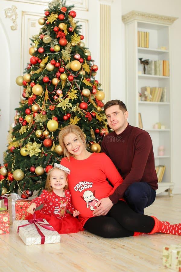 Μικρό κορίτσι που φορά την κόκκινη συνεδρίαση φορεμάτων με τον πατέρα και την έγκυο μητέρα κοντά στο χριστουγεννιάτικο δέντρο και στοκ εικόνες