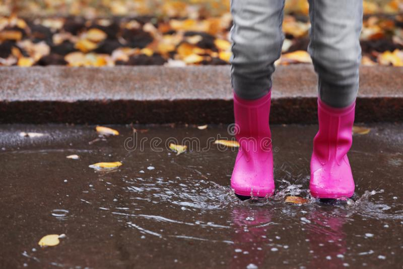 Μικρό κορίτσι που φορά τις λαστιχένιες μπότες που καταβρέχουν στη λακκούβα τη βροχερή ημέρα, εστίαση των ποδιών στοκ φωτογραφία
