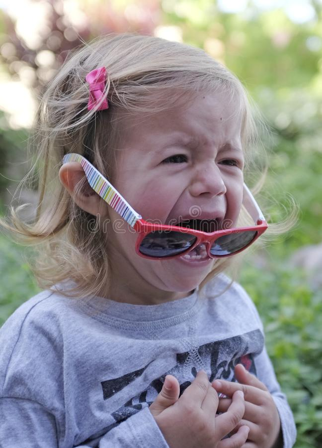 Μικρό κορίτσι που φωνάζει στον κήπο στο υπόβαθρο άνοιξη Λυπημένη καιη έννοια στοκ εικόνες
