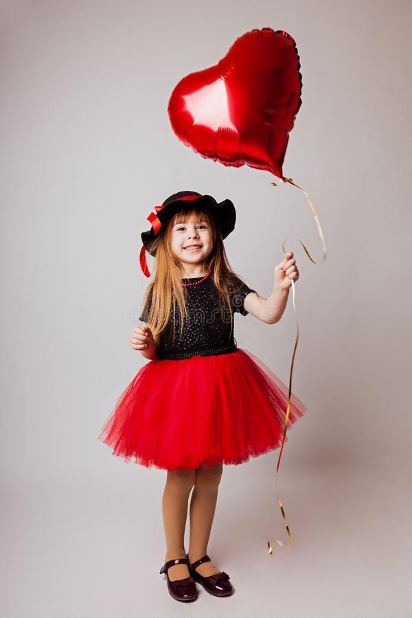 Μικρό κορίτσι που χαμογελά σε ένα μαύρα κόκκινα φόρεμα και ένα μαύρο καπέλο με ένα Πε στοκ φωτογραφία με δικαίωμα ελεύθερης χρήσης