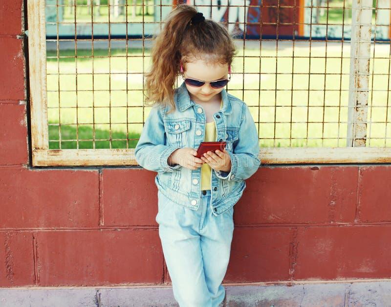 Μικρό κορίτσι που χρησιμοποιεί το smartphone, μοντέρνη φθορά παιδιών τζιν clotes στοκ εικόνα με δικαίωμα ελεύθερης χρήσης
