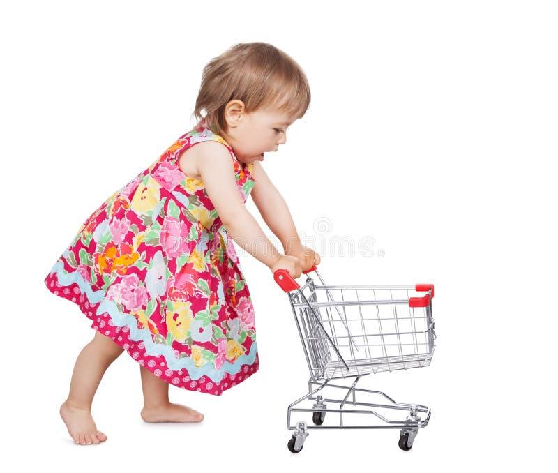 Μικρό κορίτσι που ωθεί ένα καροτσάκι στοκ εικόνες
