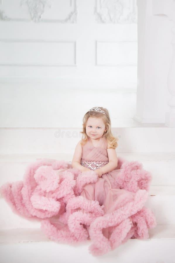 Μικρό κορίτσι, πριγκήπισσα με την κορώνα στο ρόδινο φόρεμα νεράιδων εσωτερικός στοκ εικόνα με δικαίωμα ελεύθερης χρήσης