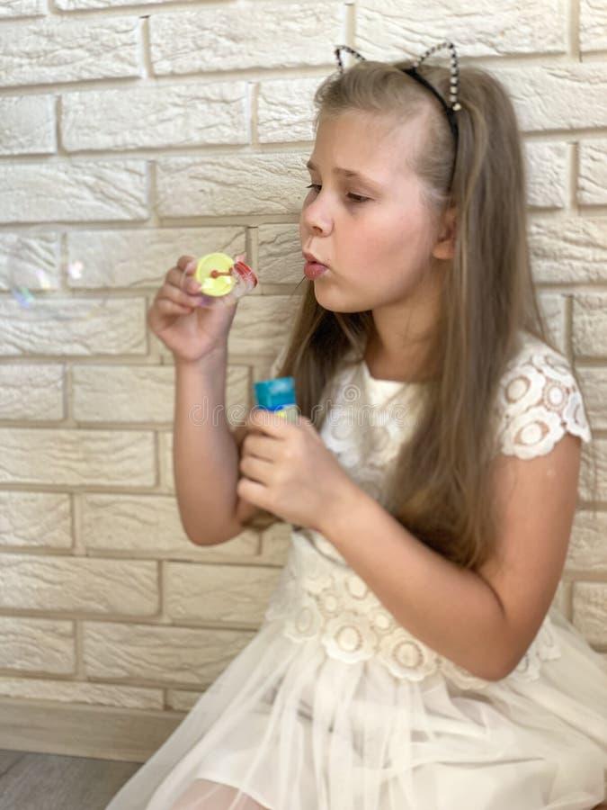 Μικρό κορίτσι σε ένα άσπρο φόρεμα Ένα κορίτσι με τα παιχνίδια στοκ φωτογραφία με δικαίωμα ελεύθερης χρήσης