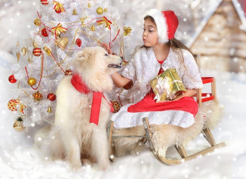 Μικρό κορίτσι σε ένα έλκηθρο με ένα δώρο Χριστουγέννων στοκ εικόνα