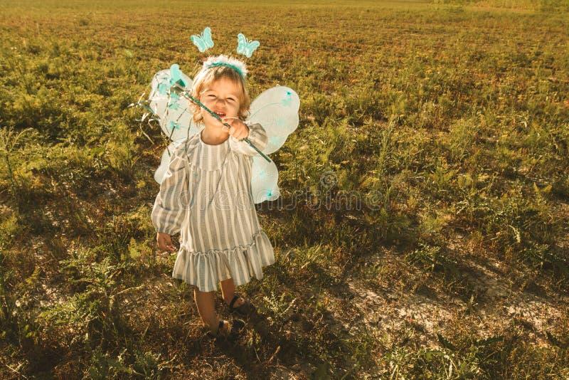 Μικρό κορίτσι σε ένα κοστούμι πεταλούδων με τα φτερά στον τομέα στοκ φωτογραφία με δικαίωμα ελεύθερης χρήσης