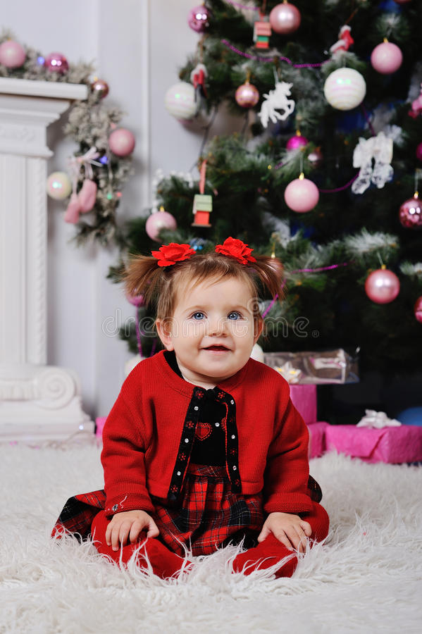 Μικρό κορίτσι σε ένα κόκκινο φόρεμα στο υπόβαθρο του χριστουγεννιάτικου δέντρου στοκ εικόνες