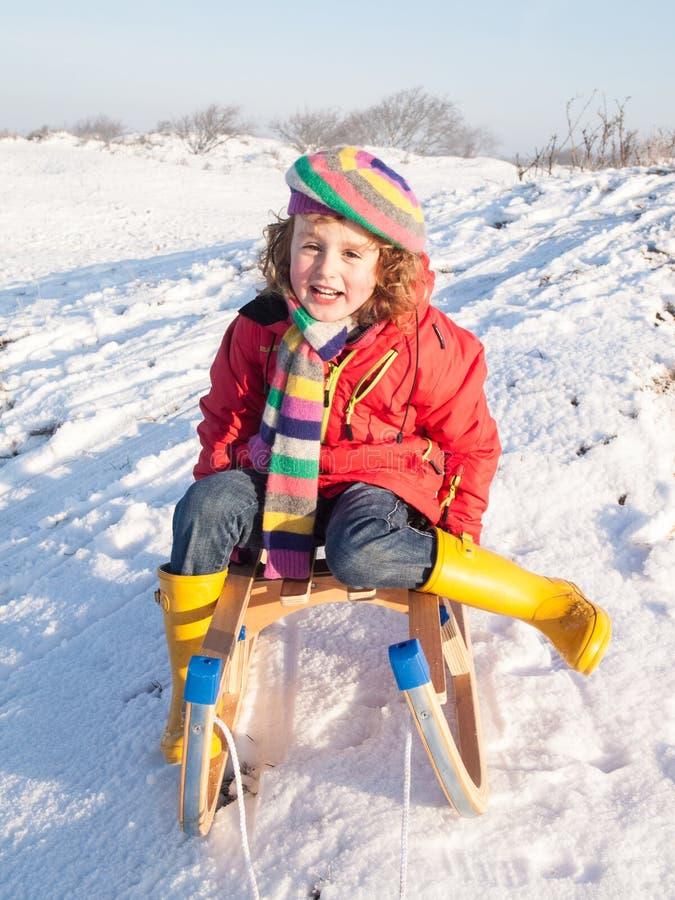 Μικρό κορίτσι σε ένα ξύλινο έλκηθρο στοκ φωτογραφία με δικαίωμα ελεύθερης χρήσης