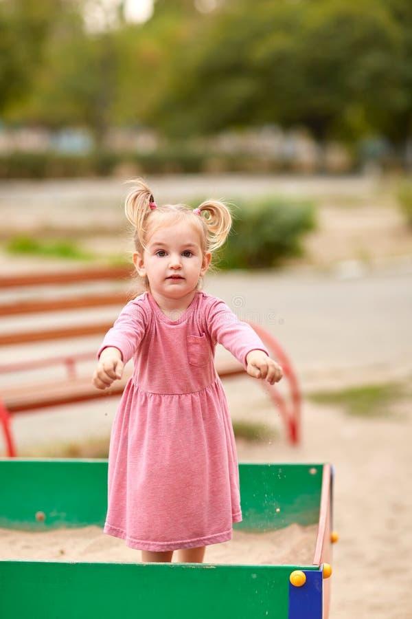 Μικρό κορίτσι σε ένα ρόδινο φόρεμα σε ένα Sandbox στοκ φωτογραφίες με δικαίωμα ελεύθερης χρήσης