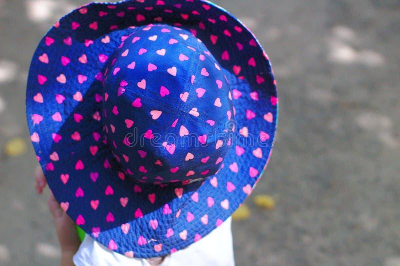 μικρό κορίτσι σε ένα όμορφο μπλε καπέλο μωρών με τις καρδιές το καλοκαίρι στοκ εικόνα