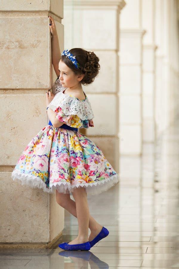 Μικρό κορίτσι σε ένα όμορφο φόρεμα κοντά στον τοίχο υπαίθρια στοκ φωτογραφίες