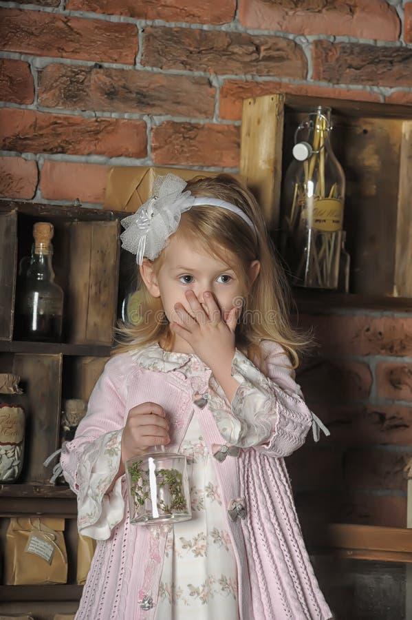 Μικρό κορίτσι σε μια ρόδινη συνεδρίαση φορεμάτων στην αναδρομική κουζίνα στοκ φωτογραφία με δικαίωμα ελεύθερης χρήσης