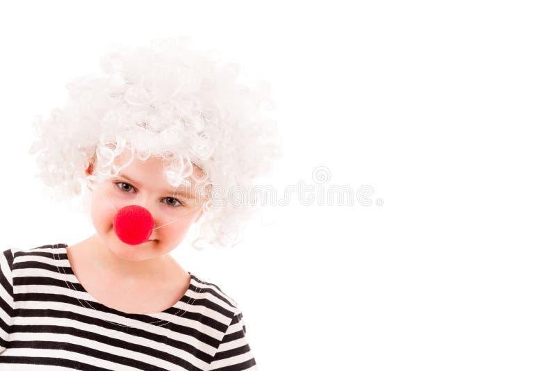 Μικρό κορίτσι στην άσπρη σγουρή περούκα κλόουν και την κόκκινη μύτη στοκ φωτογραφίες