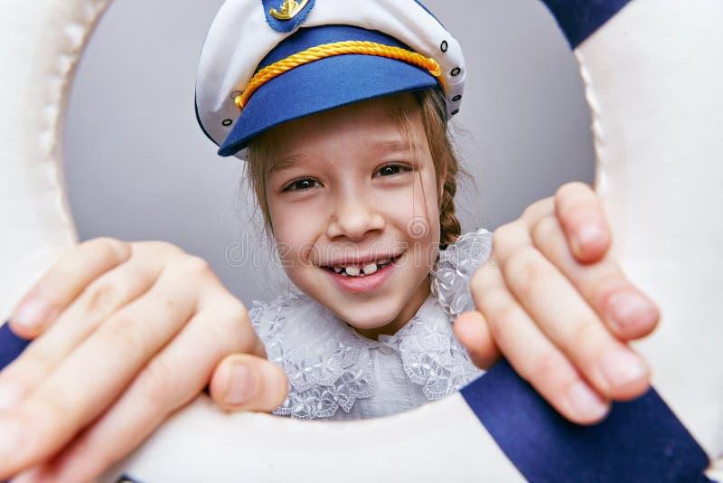 Μικρό κορίτσι στην ΚΑΠ ενός καπετάνιου που κοιτάζει κατευθείαν στοκ φωτογραφίες