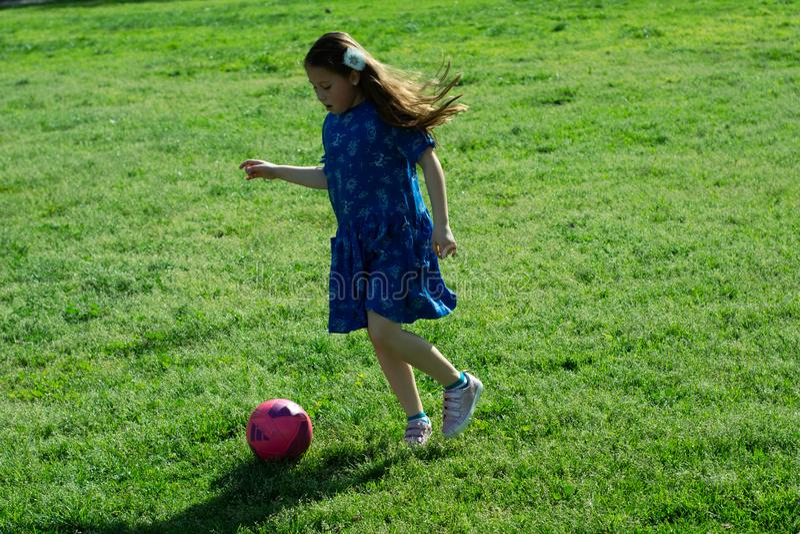 Μικρό κορίτσι στην μπλε σφαίρα ποδοσφαίρου λακτίσματος φορεμάτων στην πράσινη χλόη στοκ φωτογραφίες