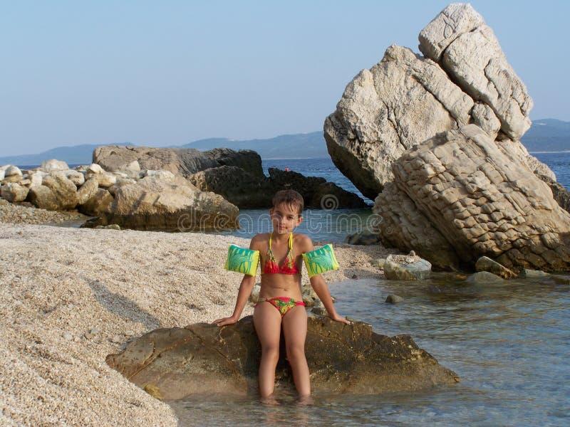 Μικρό κορίτσι στην τοποθέτηση κοστουμιών κολύμβησης στη δύσκολη παραλία στοκ φωτογραφία με δικαίωμα ελεύθερης χρήσης