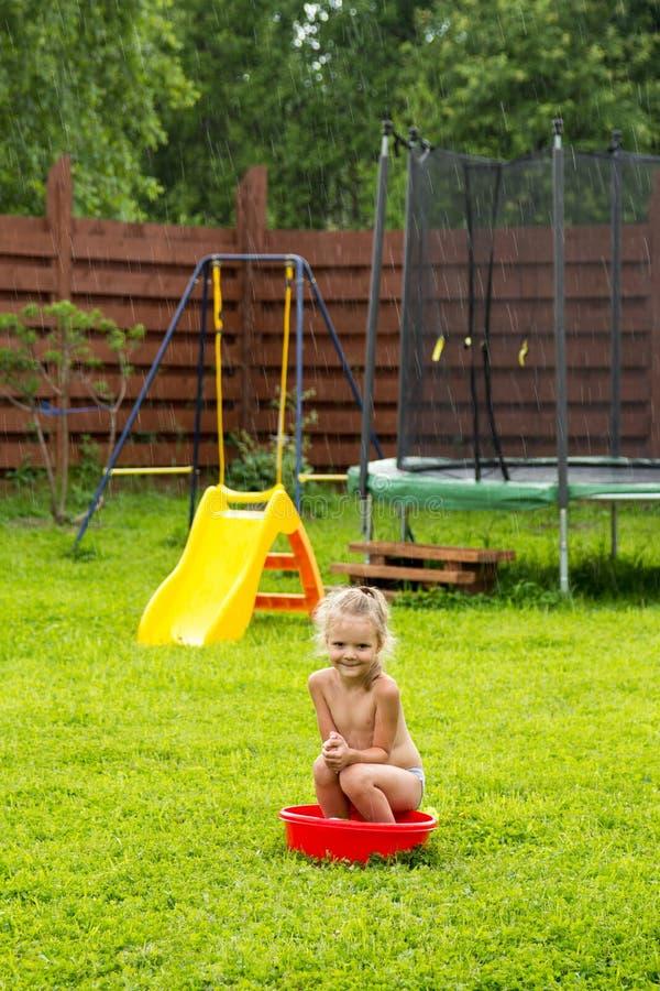 Μικρό κορίτσι στη βροχή σε μια κόκκινη λεκάνη στη χλόη στοκ εικόνα με δικαίωμα ελεύθερης χρήσης