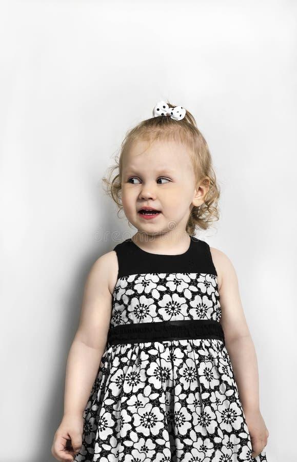 Μικρό κορίτσι στη γραπτή στάση φορεμάτων στοκ εικόνα