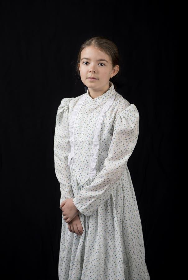 Μικρό κορίτσι στον εκλεκτής ποιότητας ιματισμό, ιματισμός ύφους πρωτοπόρων και hairstyle στοκ εικόνα με δικαίωμα ελεύθερης χρήσης