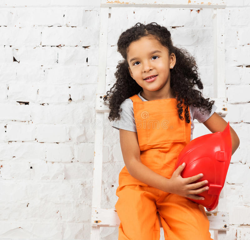Μικρό κορίτσι στον επισκευαστή ομοιόμορφο με το κράνος στα χέρια στοκ εικόνα με δικαίωμα ελεύθερης χρήσης