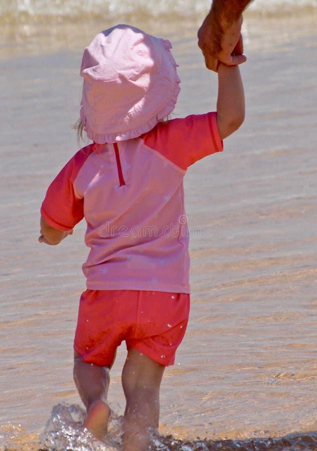 Μικρό κορίτσι στον ωκεανό στα ρόδινα ενδύματα στοκ εικόνα
