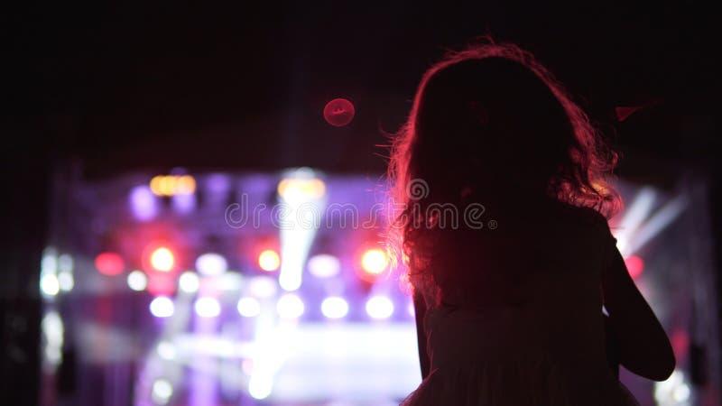Μικρό κορίτσι στον ώμο πατέρων της ` s που προσέχει και ενθαρρυντικό στο ακροατήριο κατά τη διάρκεια της συναυλίας στοκ εικόνα με δικαίωμα ελεύθερης χρήσης