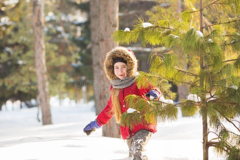 Μικρό κορίτσι στους κόκκινους περιπάτους σακακιών πρόθυμα στο χιόνι στο ξύλο στοκ εικόνα